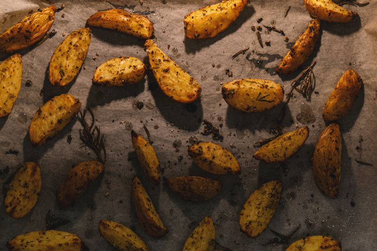 fried rosemary potato wedges on a baking tray Dinner Golden Homemade Hot Meal Potato Rosemary Salt Snack Vegetarian Baking Tray Delicious Food Fried Kitchen Oil Olive Oil Paper Pepper Roasted Rusitc Spice Tasty Thyme Vegan