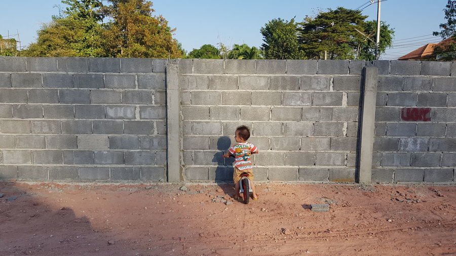 Full length of boy riding bicycle against wall