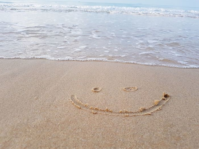Drawing a smiley face on snady beach