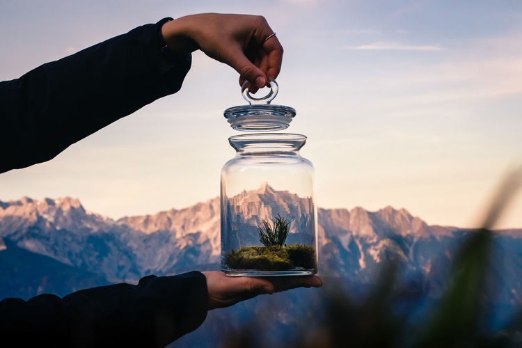 Midsection of person holding glass jar against mountain