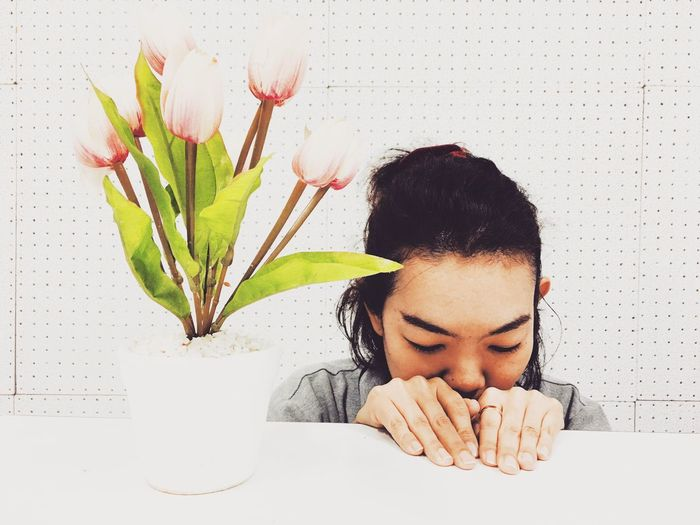Woman leaning by potted plant on table