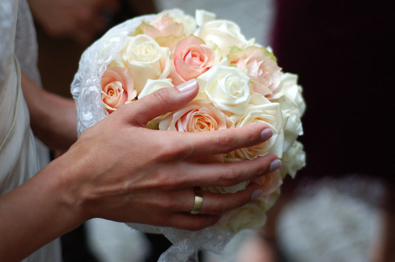 Cropped Image Of Bride Holding Rose Flower Bouquet At Wedding