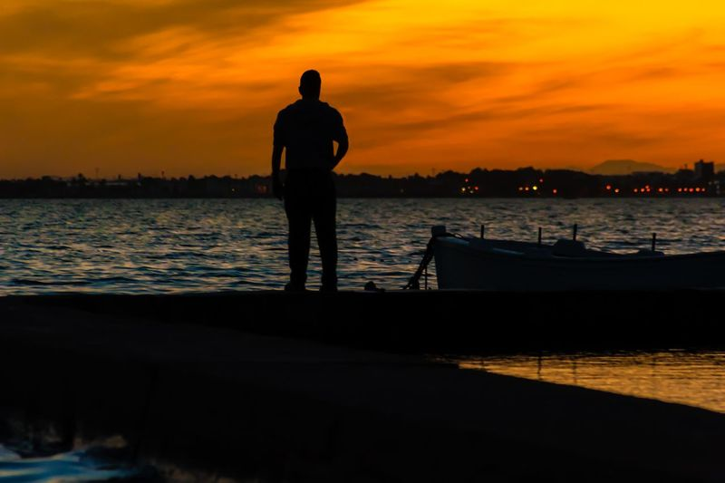 Silhouette man standing by lake against orange sky