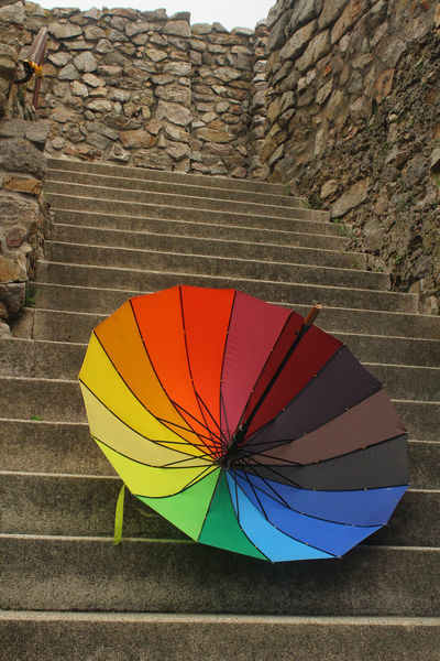 Colourful Colours Rainbow Umbrella Architecture Built Structure Close-up Colorful Colorful Umbrella Concrete Multi Colored Nature No People Orange Color Outdoors Pattern Protection Rain Rainbow Staircase Stone Wall Striped Umbrella Wall Wall - Building Feature