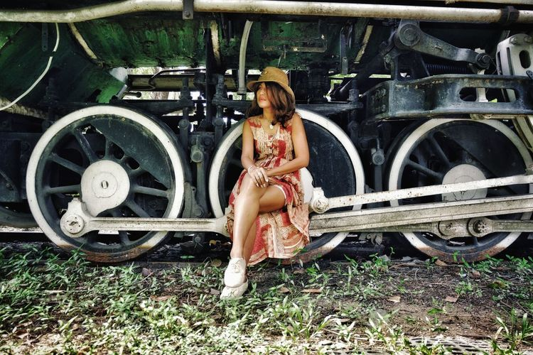 Full length of woman sitting on abandoned train