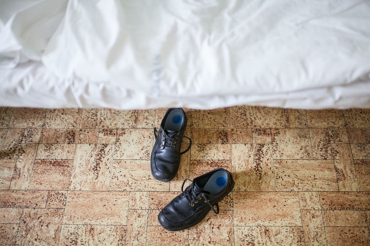 Pair of black shoes are laying under the white hospital bed. Bed Bedroom Black Brown Close-up Feet Floor Footwear Hospital Hotel Indoors  Legs Medical No People Nobody Room Silk White