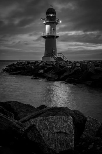 Lighthouse by sea against cloudy sky at night
