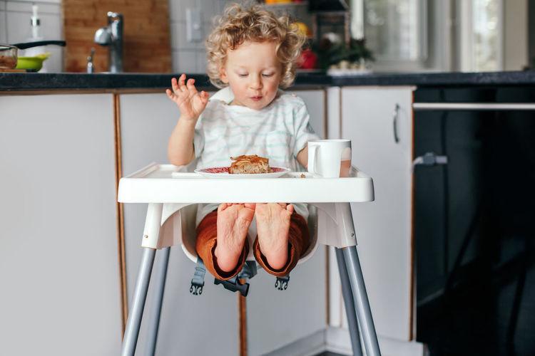 Kid boy sitting in high chair eating homemade apple pie and drinking juice. toddler enjoying food