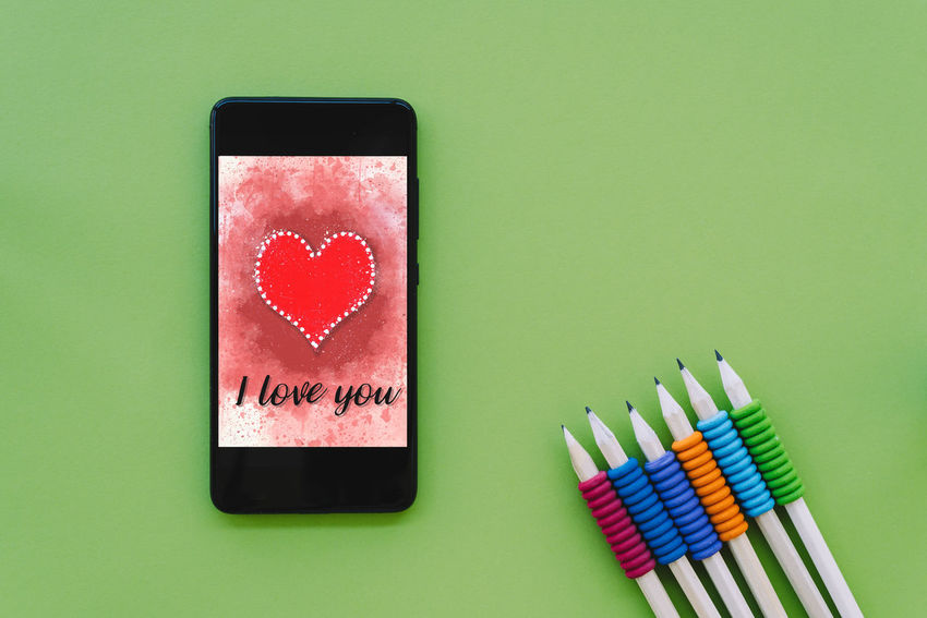 Valentines day sale background with heart illustration with the words I Love You on smartphone screen mockup on green background. View from above, flat lay App Celebration Green Greeting Love Romance Romantic Shopping Tech Valentine Valentine's Day  Above Background Communication Flat Lay Heart I Love You Mock Up Pencil Present Smart Phone Technology Valentine's Day - Holiday Valentines