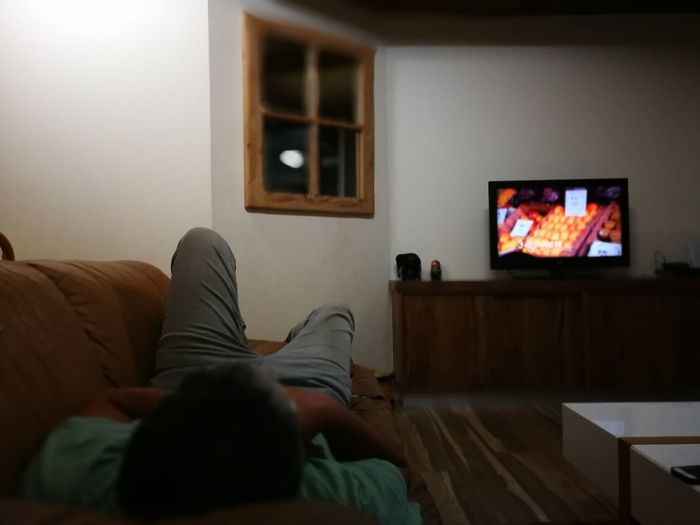 Television Set Living Room Indoors  Watching Tv Watching Home Interior One Person Flat Screen Domestic Life Lying Down Sofa Adult Adults Only Relaxation Lifestyles