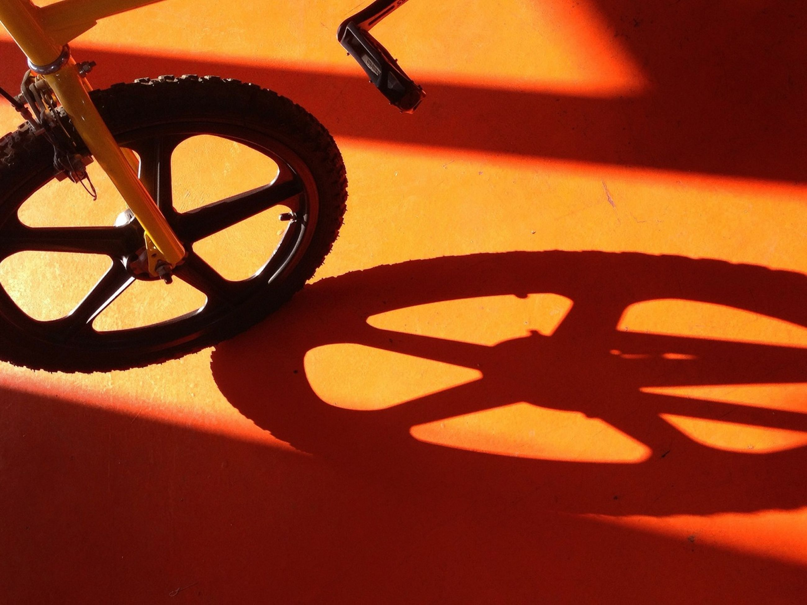 transportation, bicycle, mode of transport, orange color, close-up, land vehicle, indoors, wheel, shadow, sunset, no people, stationary, high angle view, metal, sunlight, parking, wall - building feature, still life, part of