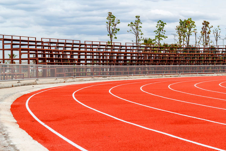 Track And Field Running Track Red No People Sport Day Cloud - Sky Sports Track Sky Nature Curve Competition Plant Outdoors Stadium Railing Empty Barrier Boundary Tree