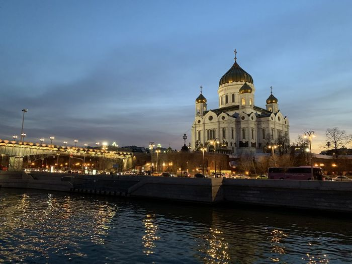 View of buildings by river in city against sky. cathedral of christ the savior