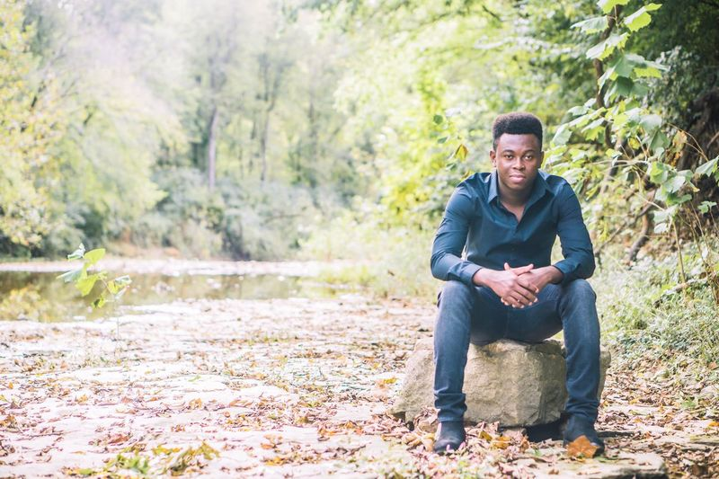 Full length of young man sitting in forest