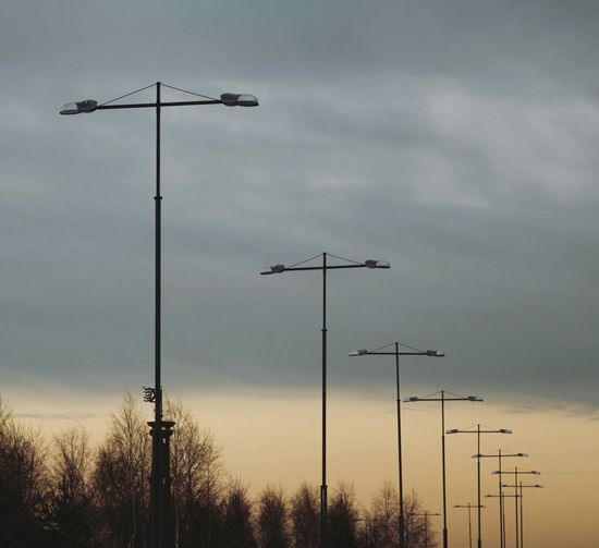 Low Angle View Of Street Lights Against Cloudy Sky