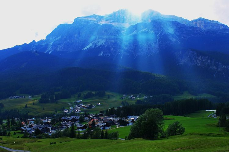 Houses On Field Against Mountains At Cortina D Ampezzo