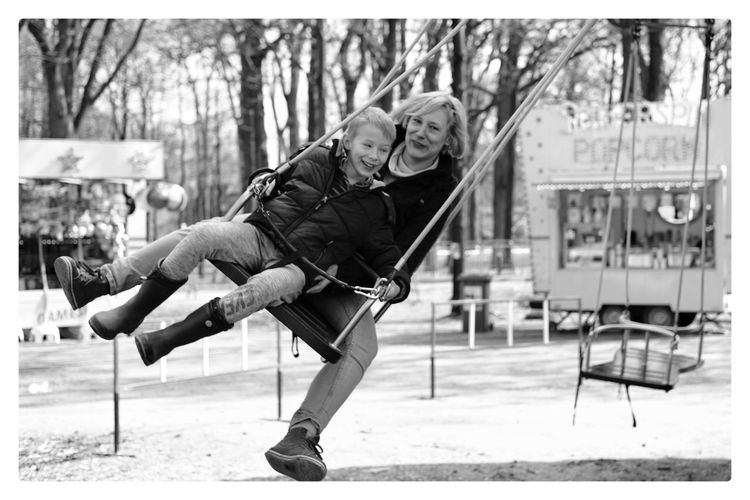 Smiling mother and son swinging at park