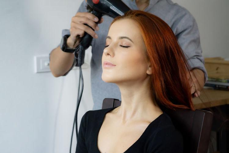 Hair stylist blow drying hair of customer