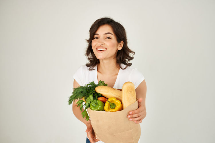 Portrait of smiling young woman holding apple against white background