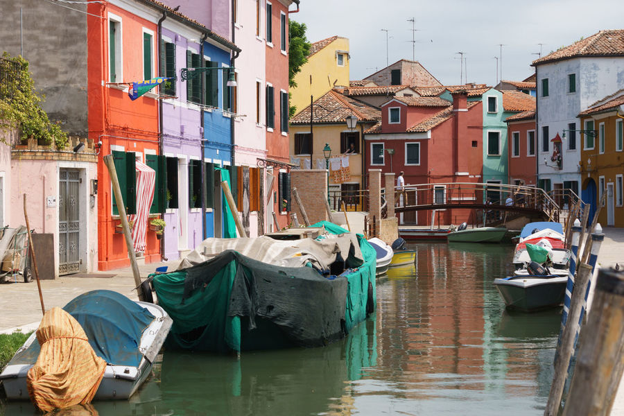 Boat Channel on Burano island, Venice, Italy Architecture Building Exterior Burano Channel Color Diversity Gondola - Traditional Boat Lifestyles Old Boat One Man Only One Person Outdoors People Relaxation Water Colour Your Horizn