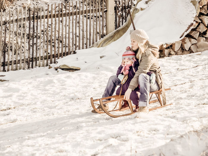 Mother and daughter sledding on snow covered field
