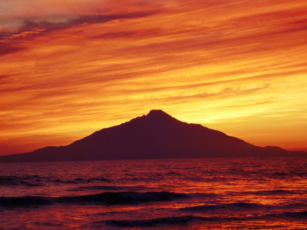 Scenic view of sea against mountain during sunset