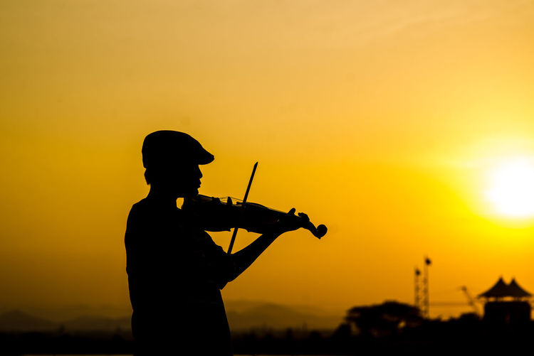 Silhouette Boy Playing Violin Against Sky During Sunset