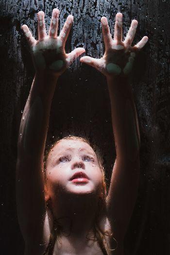 Girl seen through wet glass