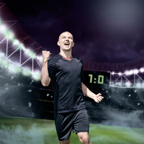 Cheerful soccer player running in stadium