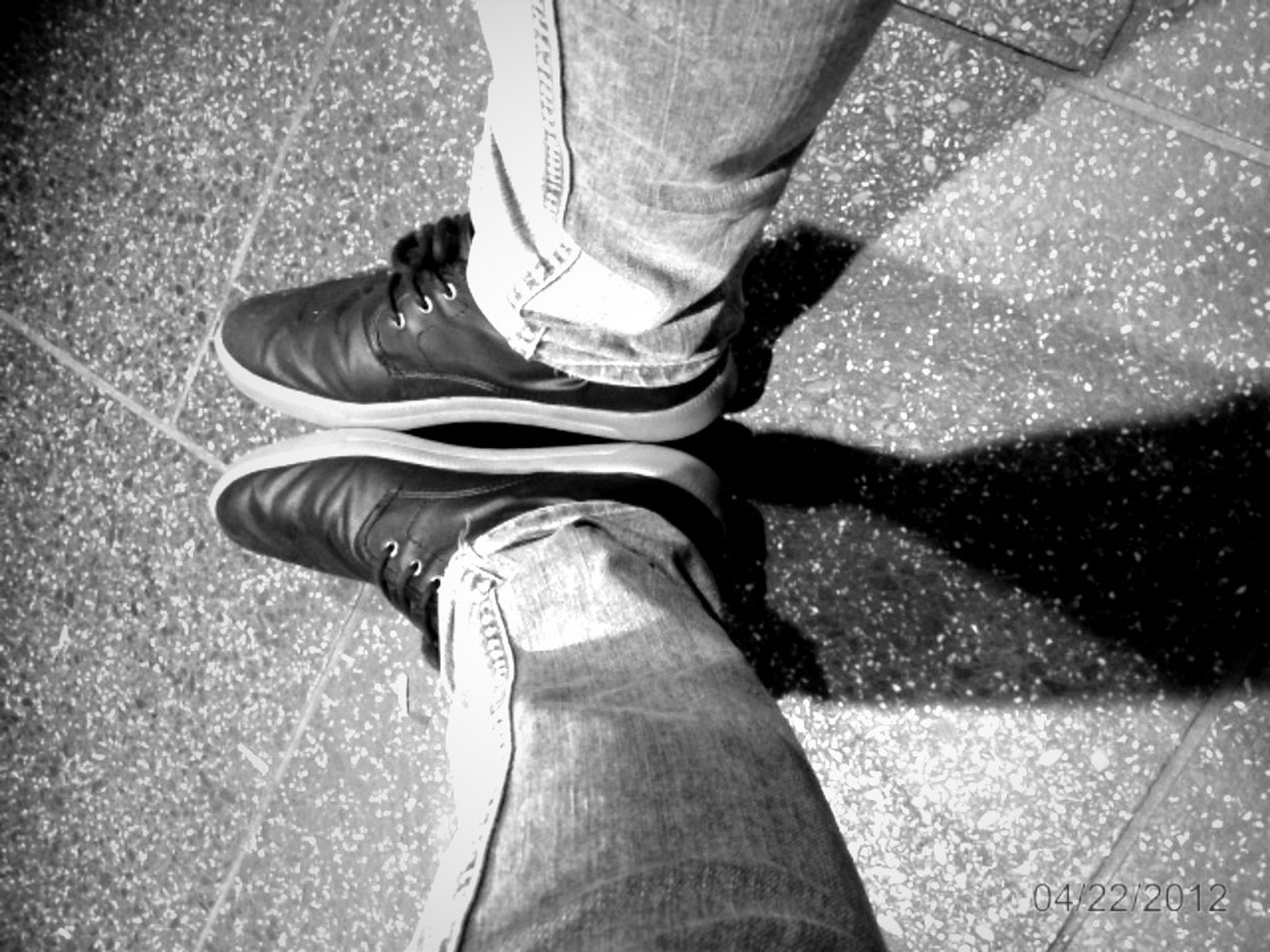 low section, person, shoe, lifestyles, jeans, standing, human foot, footwear, personal perspective, leisure activity, casual clothing, men, street, human limb, sitting, road, canvas shoe