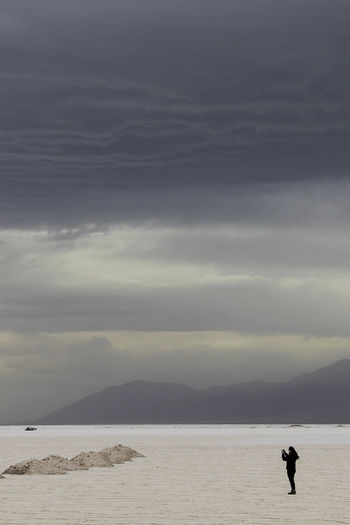 Distant view of woman at salt flat against cloudy sky
