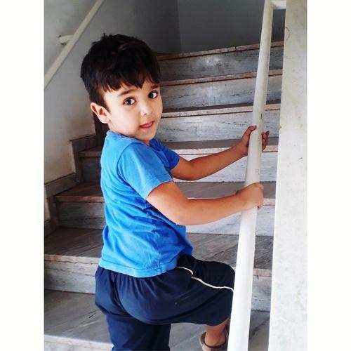 Portrait of cute boy climbing steps