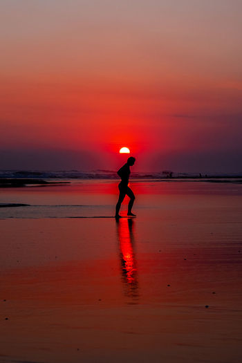 A woman walks out of the sea. Sunset Silhouettes Beach Beauty In Nature Full Length Horizon Over Water Land Leisure Activity Lifestyles Nature One Person Orange Color Real People Scenics - Nature Sea Silhouette Sky Standing Sunset Tranquility Water 2018 In One Photograph