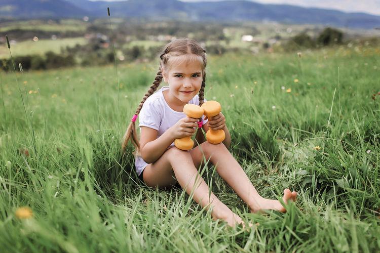 Portrait of boy holding apple on field