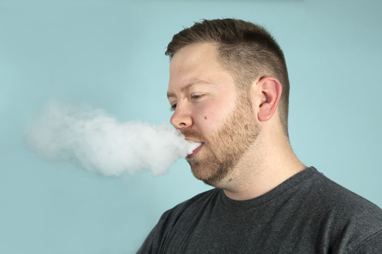 Young man exhaling smoke against blue background