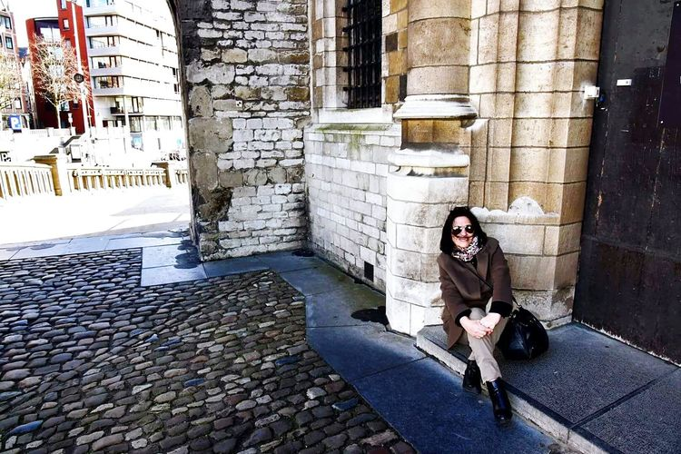 Woman sitting near an old building