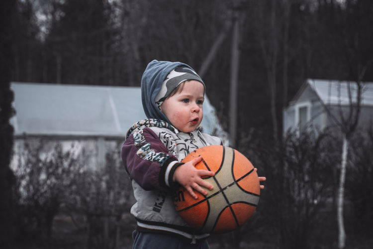 Cute boy playing with ball against trees