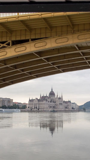 Hungarian Parliament Building By Danube River Seen Through Arch Bridge