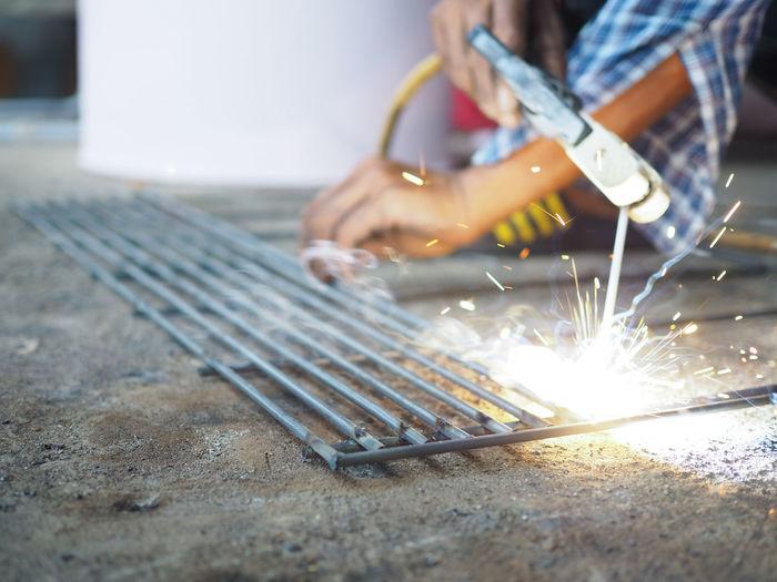 Cropped Hands Of Welder Welding Metal In Workshop