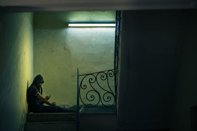 Side view of man sitting by window