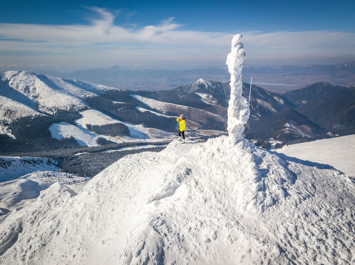 Mid distance view of woman standing on snowcapped mountain