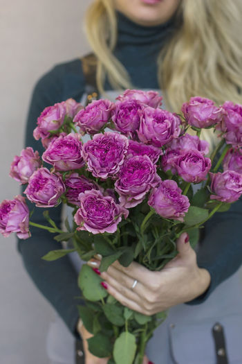 Close-up of woman holding pink roses
