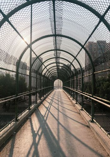 View of footbridge through chainlink fence