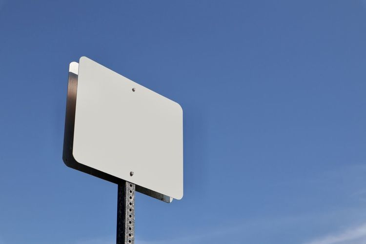 blank white street sign against blue sky Sky Low Angle View No People Blank Copy Space Road Sign Sign Communication Nature Blue Direction Day Clear Sky Outdoors Road White Color Arrow Symbol Guidance Pole Technology Blank Space Graphic Resource