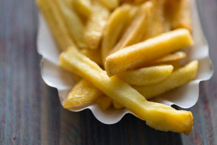 Close-Up Of French Fries In Paper Plate On Table