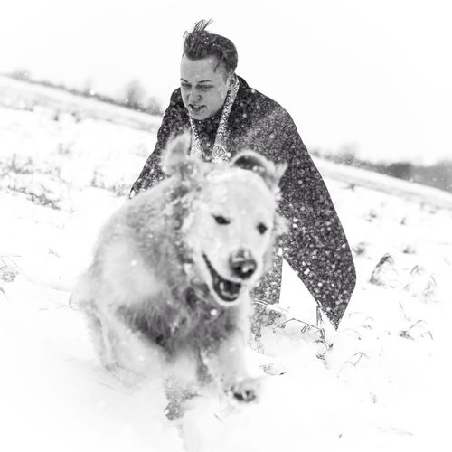 Portrait of young man with dog on snow