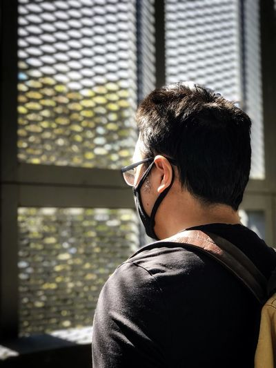 Rear view of young man wearing glasses against window.