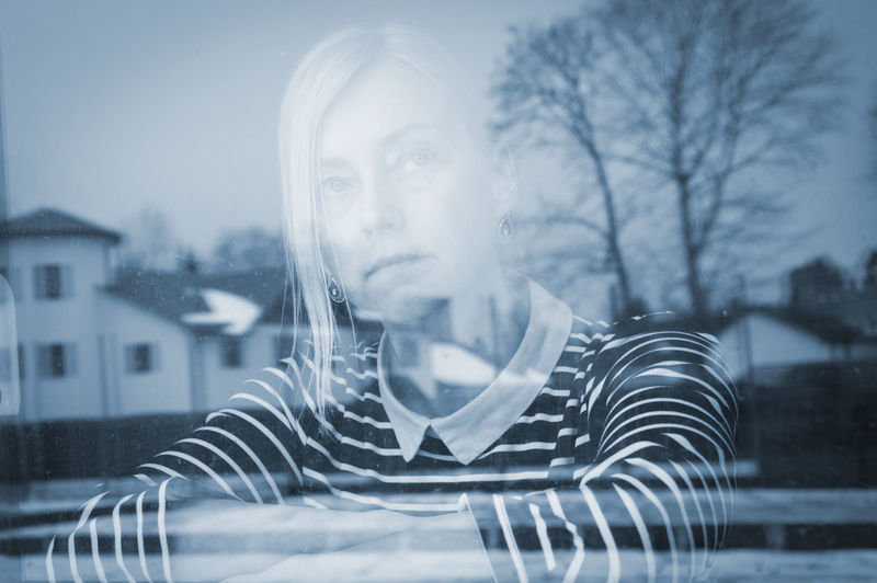 Close-up of woman looking through window