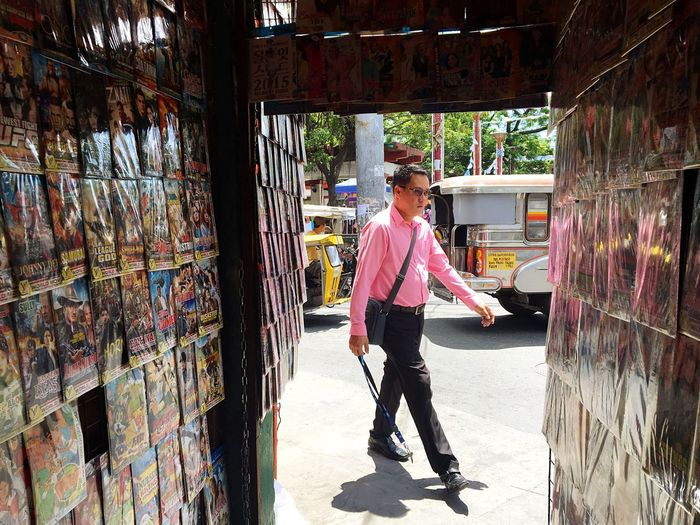 A man in pink shirt walks past a shop selling fake DVDs and Blu-ray movies in Taguig, Metro Manila. Full Length One Person Indoors  Adult One Man Only Day DVD Blueray Counterfeit Pink Shirt Pink Fake Philippines Taguig Manila The Street Photographer - 2017 EyeEm Awards