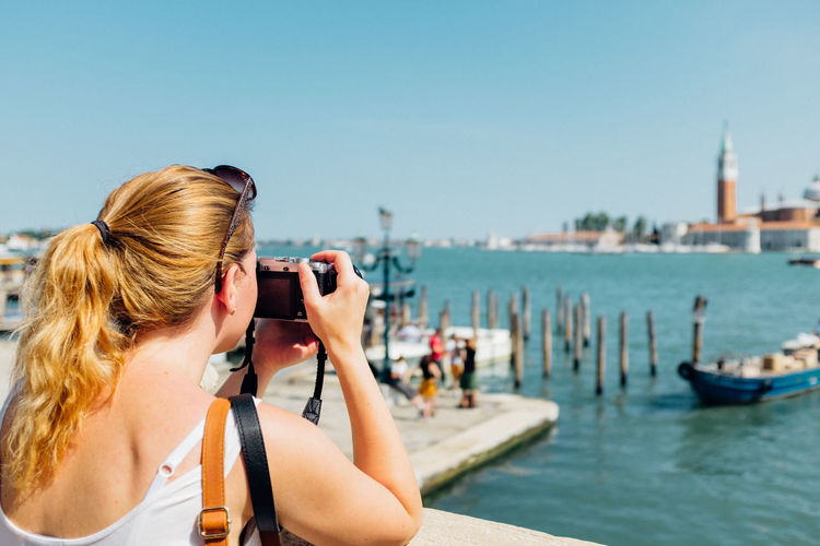 Woman photographing in harbor